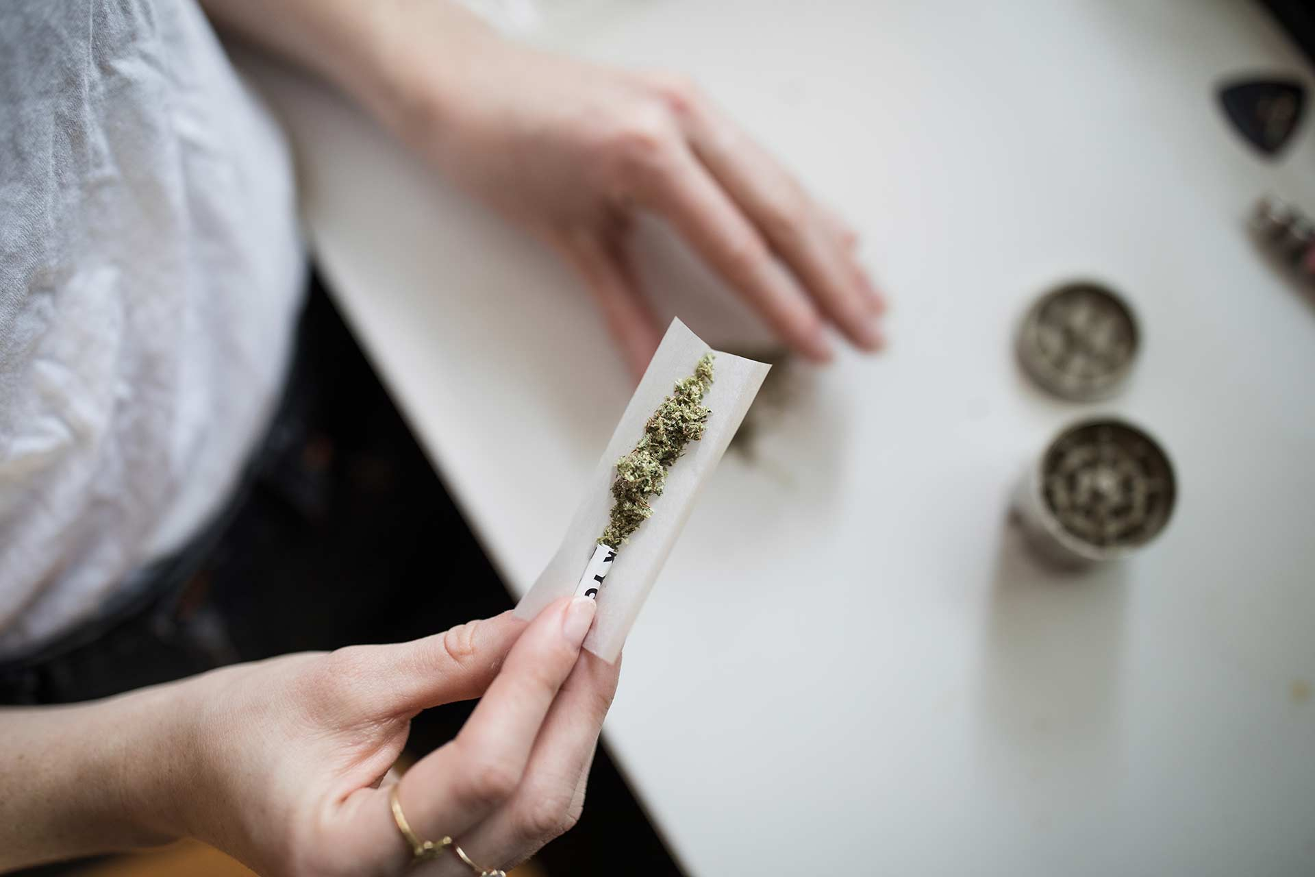 woman holding an unrolled joint
